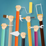 Many hands holds up instruments and tools. Stock Images