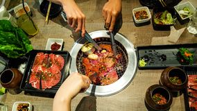 Many hands of people are grilling Japanese buffet that consist of meat and vegetable on the hot charcoal. In the restaurant stock photos