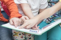 Many hands point into a book. Many children hands point to the letter in the primer, close-up stock images