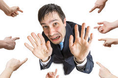Many hands are pointing and blame stressed man. Isolated on white background. View from top.  stock images