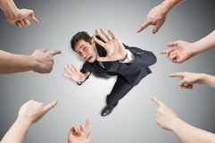 Many hands are pointing and blame stressed man. View from top stock images