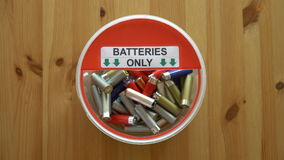 Many hands putting lot of used batteries in the recycling box. Top view. Close up stock video