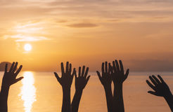 Many hands raised against sunset sky. At sunset Stock Photos