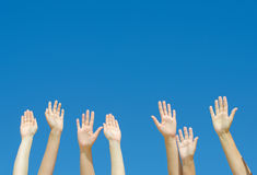 Many hands raised up. Against the blue sky royalty free stock photography