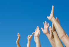 Many hands raised up. Against the blue sky royalty free stock photos