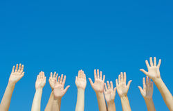Many hands raised up. Against the blue sky stock photography