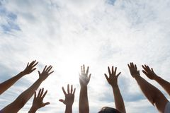 Many hands raised up against the blue sky. Friendship. Teamwork concept royalty free stock images