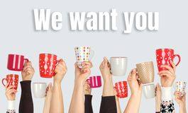 many hands raised up and holding ceramic cups on a gray background, inscription we want you royalty free stock photography