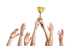 Many hands raised up. Winner is holding trophy in hands. Isolated on white background Stock Photo