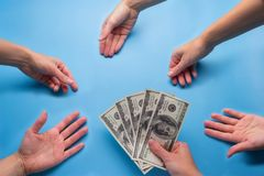 many hands reach for money stock image