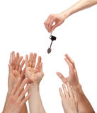 Many hands reaching out for key. Concept of winning a house, apartment, etc.; isolated on white