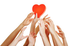 Many hands reaching for red heart Stock Photos