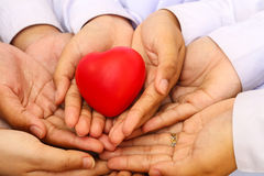 Many hands and a red heart Stock Photos