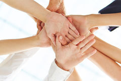 Many hands stacked for motivation stock images