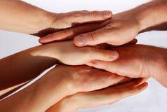 Many hands symbolizing unity and teamwork. Many hands lying upon another symbolizing teamwork, strength and power, on white stock photo