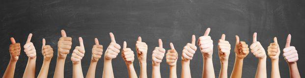 Many hands with thumbs up. In front of blackboard stock image