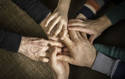 Many hands together. Interior shot stock images