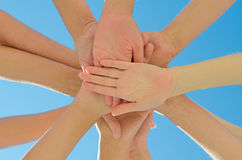 Many hands together. Over blue sky royalty free stock photography