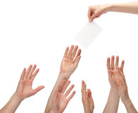 Many hands wanting to get offer. (you can write your text on a white sheet of paper); many hands reaching out for blank paper with copy space, isolated on white royalty free stock photo