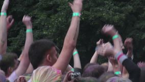 Many hands waving up in air, happy young people jumping, partying at festival