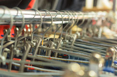 Many hangers in a row for clothes in the store. Stock Image