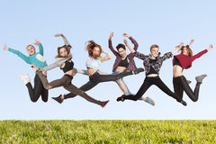 Many happiness young women jumping on the grass royalty free stock image