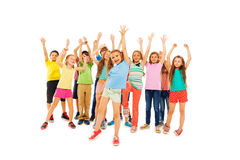 Many happy kids cheer and rise hands. Large group of many kids standing together as a crowd rising hands and cheering diverse white and black full height royalty free stock photography