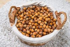 Many hazel nuts in wicker basket Stock Photos