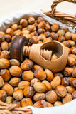 Many hazel nuts and wood cracker in wicker basket Stock Photography