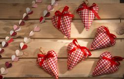 Many hearts sewn from red plaid fabric on the board Royalty Free Stock Image