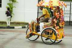 A decorated trishaw or tricycle rickshaw in historical Malacca or Melaka, Malaysia. Many of the heavily decorated cycle rickshaws Malay: beca equipped with sound royalty free stock images