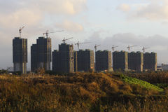 Many high-rise buildings under construction in the fields in the sunset near Shanghai Stock Image
