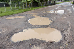 Many hole and flooding on asphalt road Royalty Free Stock Photos