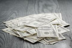Many hundred dollar bills on wooden table Royalty Free Stock Photography