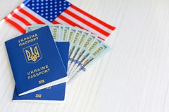 Many hundred dollars and two Ukrainian blue passports. Immigration to the United States concept. Ukrainian foreign passport. Royalty Free Stock Photography