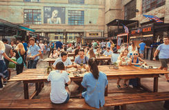 Many hungry people eating meals around tables outdoor. KYIV, UKRAINE - JUL 23: Many hungry people eating meals around tables outdoor during Street Food Festival Royalty Free Stock Photo