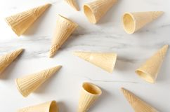 Many of ice cream cones on white table.Ice cream cones pattern. Top view of vanilla ice cream in waffle cones.Tasty summer food stock photo