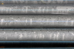 Many industrial black plastic pipes with water drops. Royalty Free Stock Photography