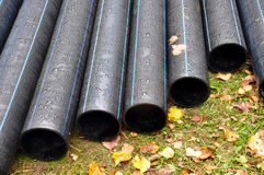 Many industrial black plastic pipes. Stock Photo