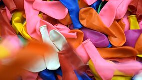 Many inflatable balloons of colors, deflated in a pile, colorful background 3