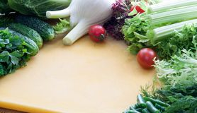 Ingredients for cooking vegetarian food from greens and vegetables on a yellow board royalty free stock photos