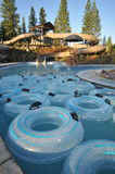 Many inner tubes floating in pool at water park Stock Photos