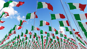Many Italy flags on flagpoles against blue sky. Stock Image