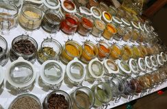 Many jars with spices and dried aromatic herbs gathered all over royalty free stock image