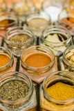 Lots of colorful tasty seasoning spices in glass jars. Many jars of tasty colorful seasoning herbs and spices. Vertical standing photo Stock Photos