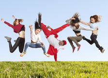 Many jumping happiness people on the grass stock image