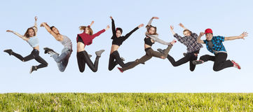 Many jumping people on the grass stock images