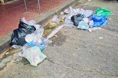 Many junk is on the street and footpath. Garbage such as plastic, foam, bottle. Dirty waste and bad smell. stock images
