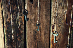 Many keys hanging on a string. Wooden background. Selective focus Royalty Free Stock Images