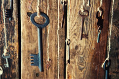 Many keys hanging on a string. Wooden background. Selective focus Stock Photo